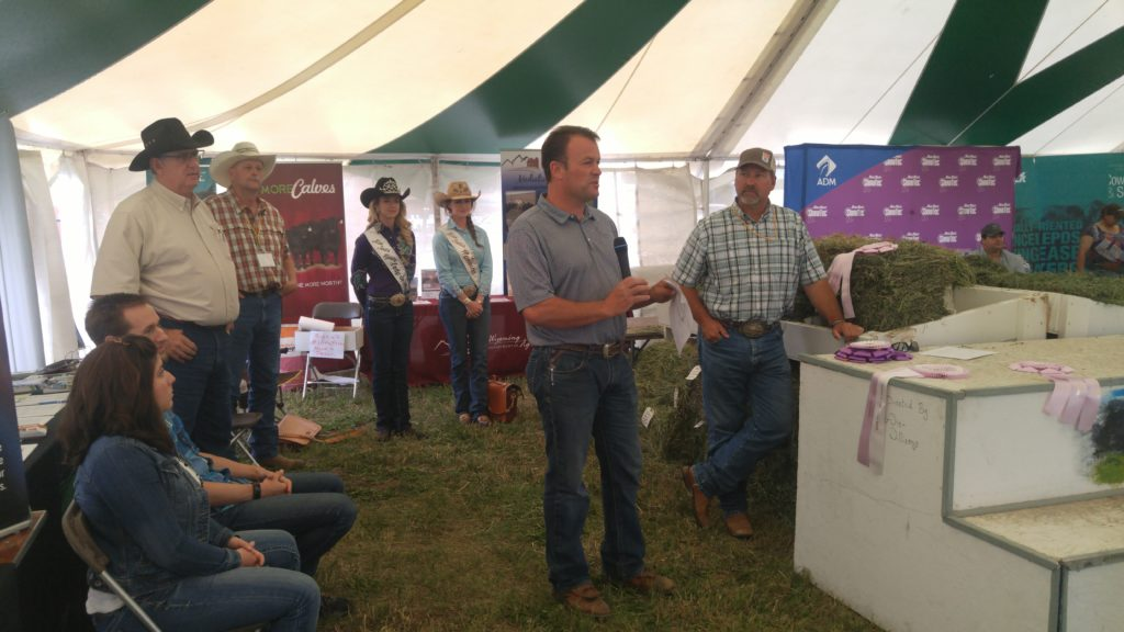 Brian Wing, President of the Wyoming Hay and Forage Association talks at the awards ceremony on Tuesday afternoon. Morgan Wallace (left), 2018 Miss Rodeo Wyoming, Abby Hayduck (right), Miss Rodeo Wyoming 2017, and ? (right of Brian), from Brown Company were all present to present awards.